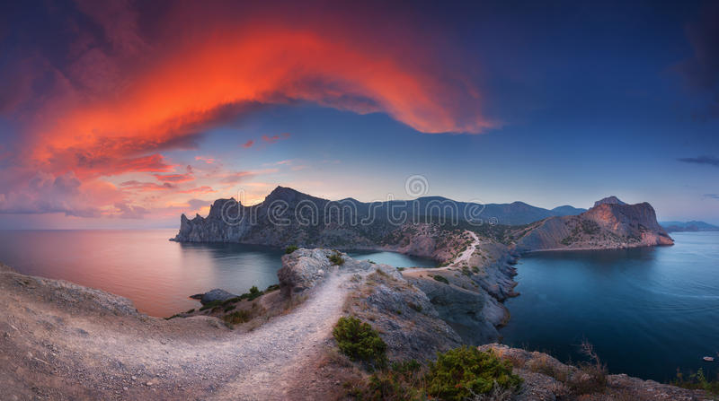 Beautiful panoramic landscape with mountains, sea at sunset. Beautiful panoramic landscape with mountains, sea, blue sky and beautiful colorful red clouds at stock photography