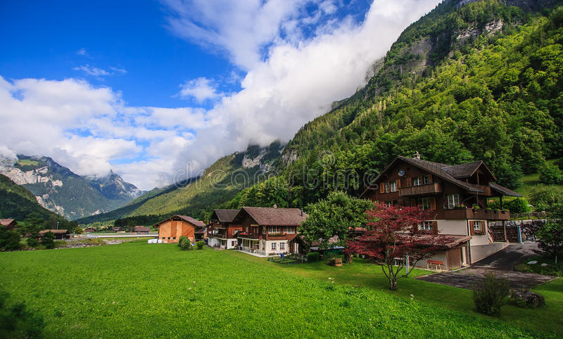 Beautiful panoramic postcard view of picturesque rural mountain scenery in the Alps with traditional old alpine mountain chalets stock images