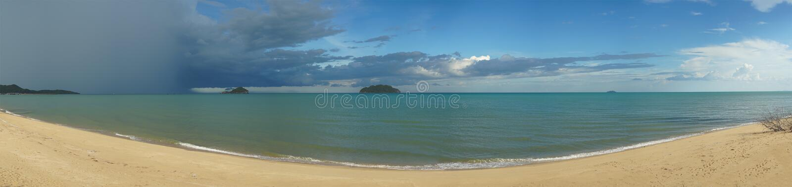 Beautiful panoramic sea view and clean beach wth three island and rainy cloud coming from left side of picture, colouful blue stock photography