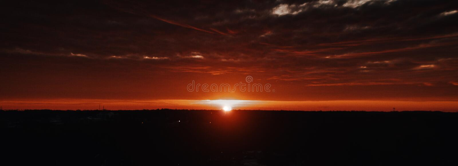 Beautiful panoramic shot of the dark hills with the sun shining on the horizon with cloudy skies. A beautiful panoramic shot of the dark hills with the sun stock photography