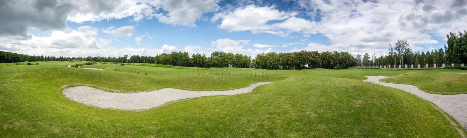 Beautiful panoramic shot of golf course at sunny day. Beautiful panoramic shot of perfect golf course at sunny day royalty free stock photography