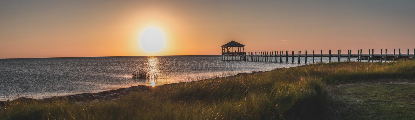 Beautiful panoramic shot of the wooden dock taken at golden hour at the beach royalty free stock image