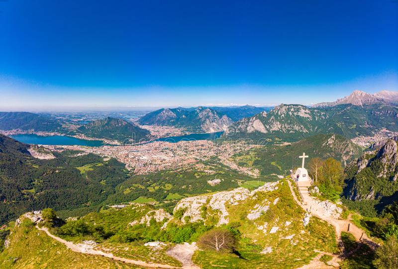 Beautiful panoramic sunrise landscape at town Lecco, lake Como in sunny summer day. Stunning airial view to cross on top of stock images