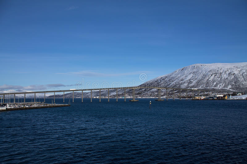 Beautiful panoramic view from boat on Tromso landscape with snowy mountains and bridge in sunny blue sky, Norway royalty free stock images