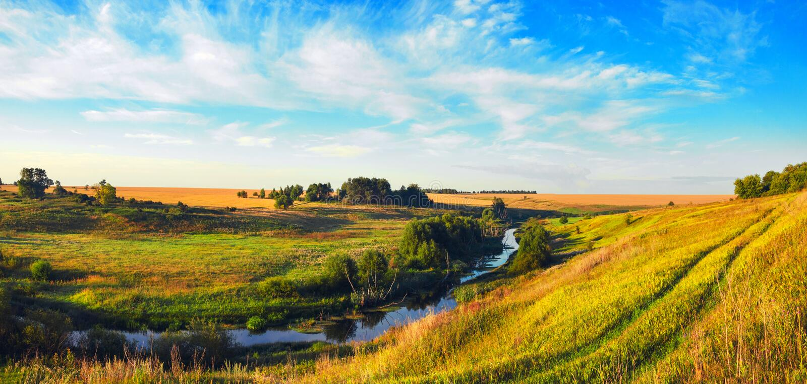 Sunny summer landscape with ground country road,river and wheat fields illuminated by the warm light of rising sun. Beautiful panoramic view and country stock images