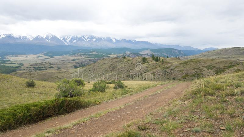 Beautiful panoramic view of the country road across the steppe in Altai. In the background, the Altai mountain range stock photos