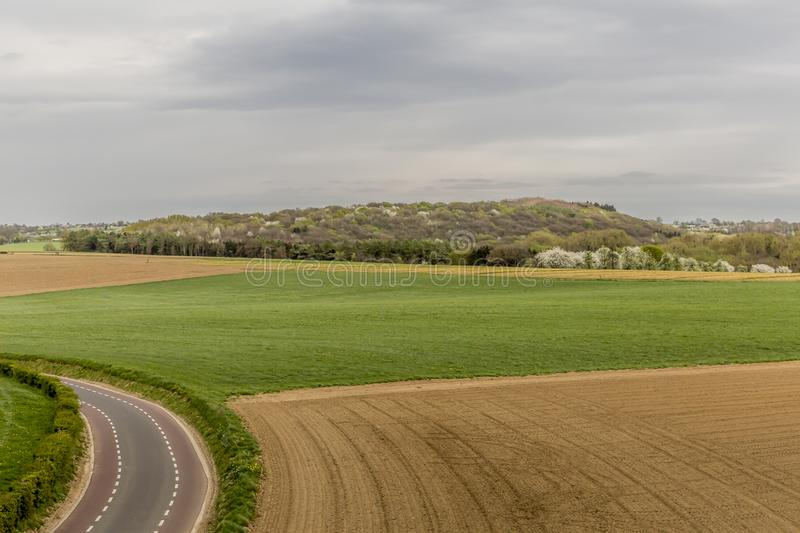 Beautiful panoramic view of a field with farm land and another one with green grass next to an asphalt road stock images