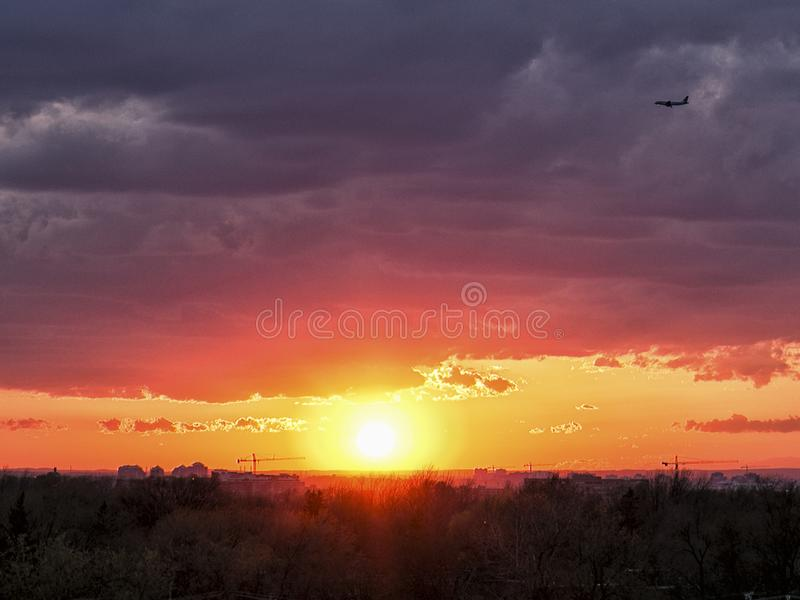 Panoramic view of a plane against purple clouds over a glorious sunset royalty free stock images