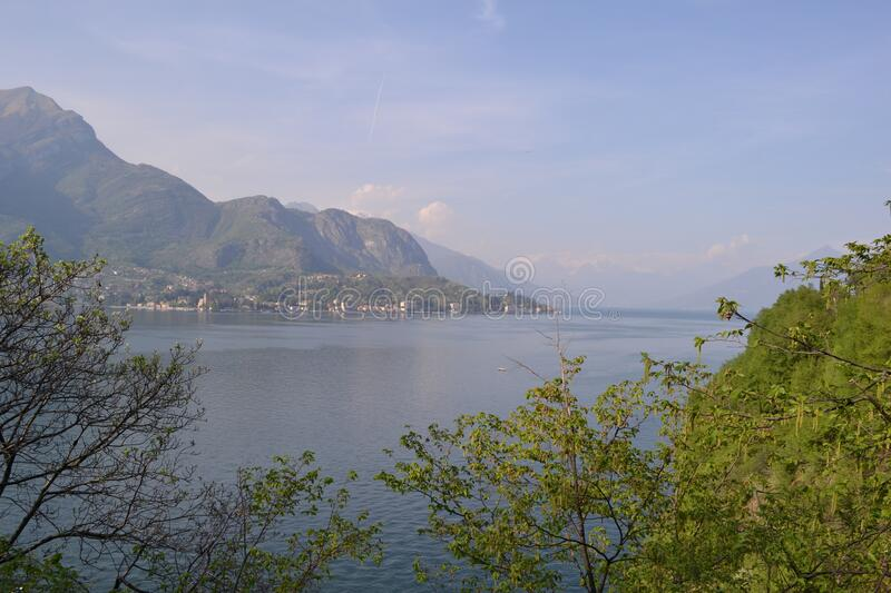 Beautiful panoramic view to the lake Como, lakefront, motorboat moving. stock photo