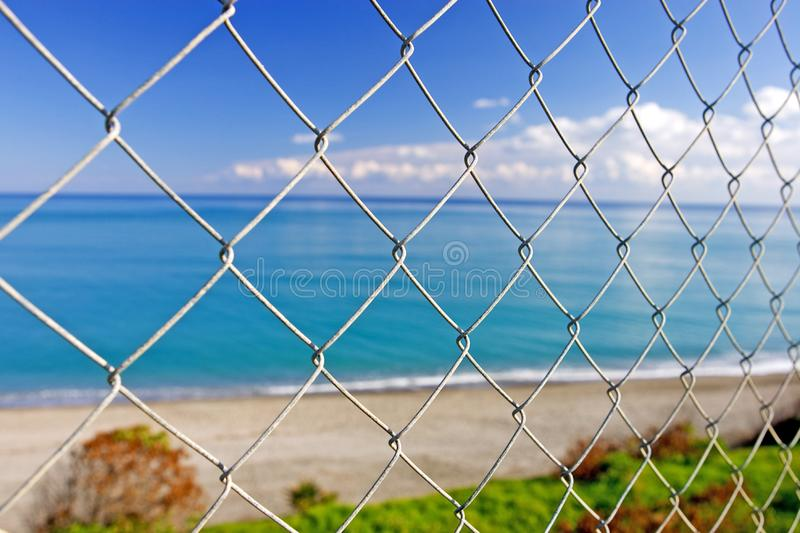 Beautiful paradise beach seen through wires of a fence