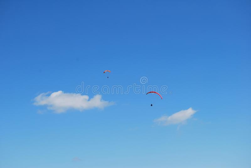Beautiful paraglider in a blue summer sky. Sportsman flying on a paraglider, extreme sports in the air stock images