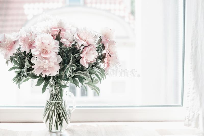 Beautiful pastel pink bouquet of peonies in glass vase on windowsill. Flowers in interior design. stock image