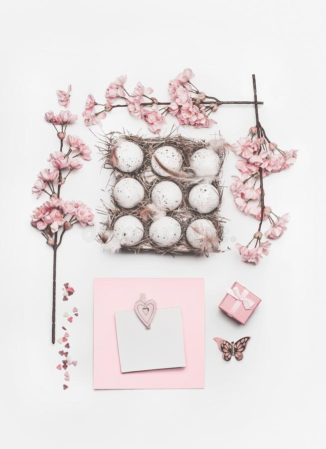 Beautiful pastel pink Easter layout with blossom decoration, hearts, eggs in carton box and greeting card mock up royalty free stock image
