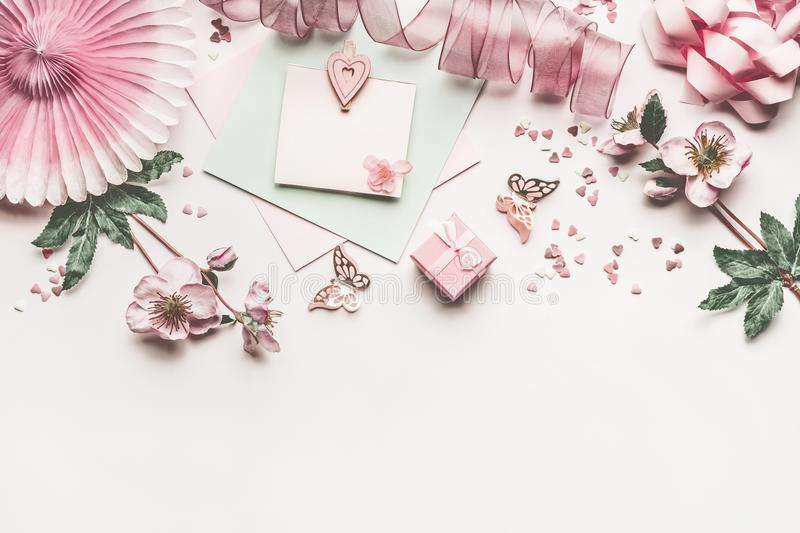 Beautiful pastel pink layout with flowers decoration, ribbon, hearts, bow and card mock up on white desk background, top view stock photos