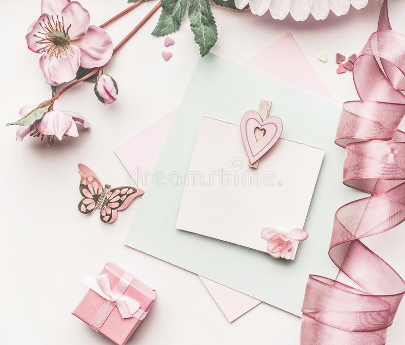 Beautiful pastel pink layout with flowers decoration,ribbon, hearts and card mock up on white desk background, top view, flat lay. royalty free stock image