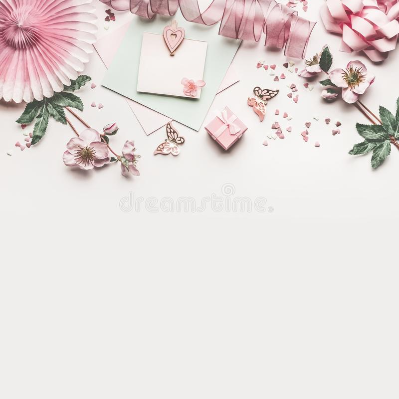 Beautiful pastel pink work space with flowers decoration,ribbon, hearts, bow and card mock up on white desk background, top view stock images