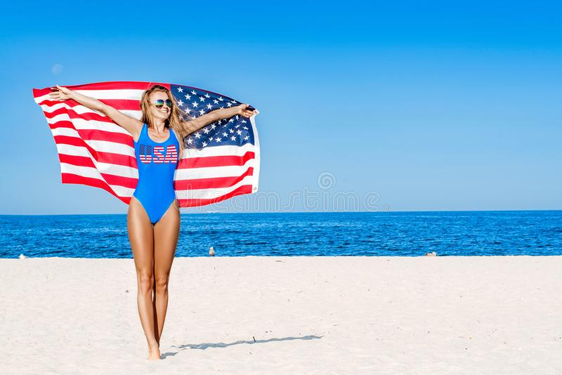 Beautiful patriotic cheerful woman holding an American flag on the beach. Beautiful patriotic happy woman with the American flag held in her outstretched hands royalty free stock images