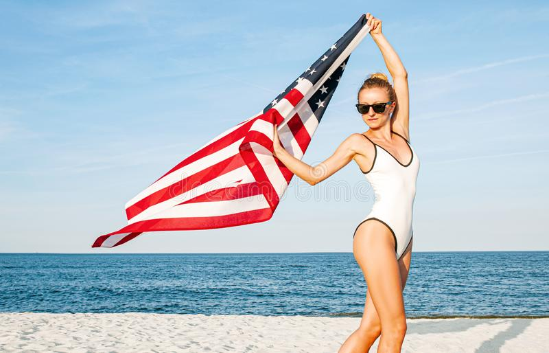 Beautiful patriotic woman holding an American flag on the beach.  USA Independence day, 4th July stock images