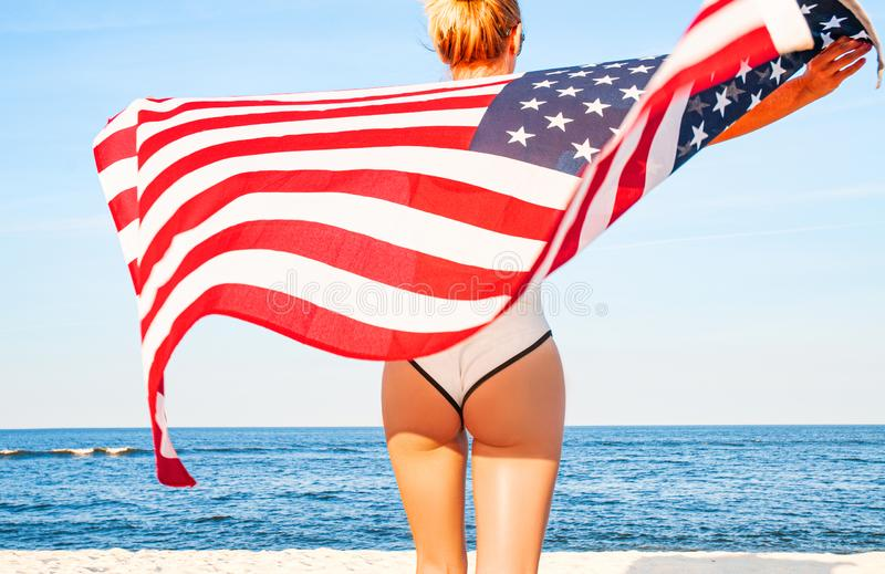 Beautiful patriotic woman holding an American flag on the beach.  USA Independence day, 4th July. Freedom concept royalty free stock photography