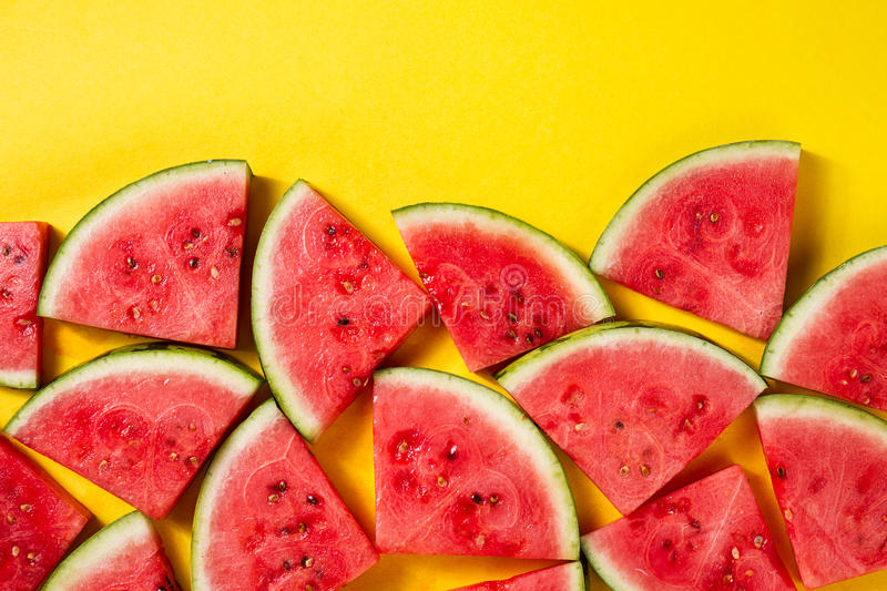 Beautiful pattern with fresh watermelon slices on yellow bright. Background. Top View. Copy Space royalty free stock photos