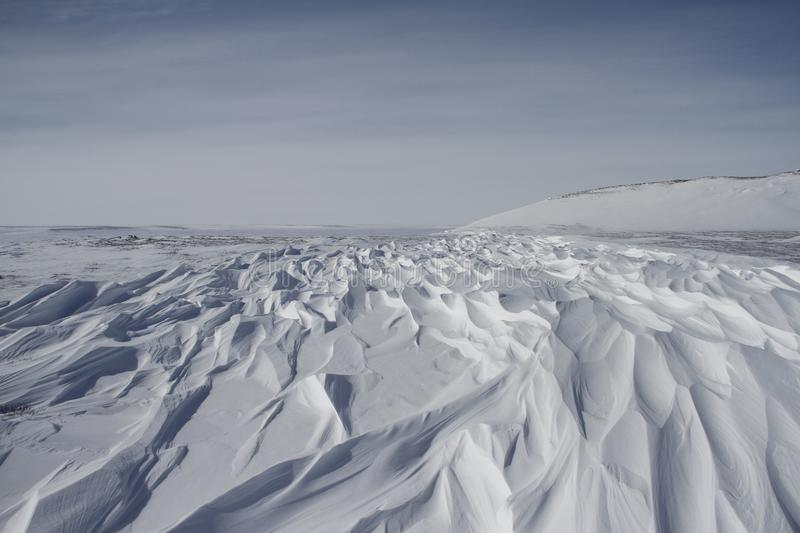 Beautiful patterns of sastrugi, parallel wavelike ridges caused by winds on surface of hard snow royalty free stock photography