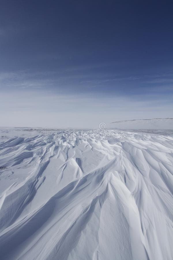 Beautiful patterns of sastrugi, parallel wavelike ridges caused by winds on surface of hard snow royalty free stock photo