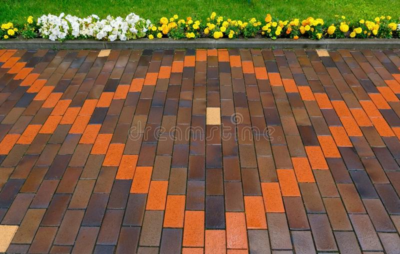 Beautiful pavement of red and brown clinker brick. Walking path. Decorated with flowers stock images