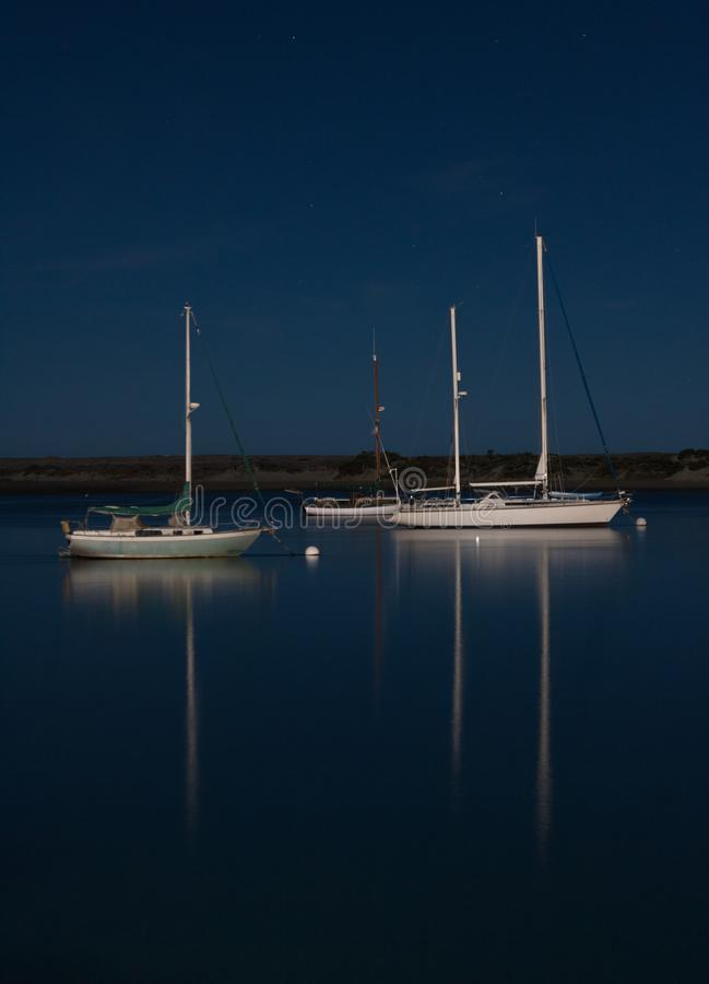 Boats reflecting on moonlit night in peaceful bay royalty free stock photo