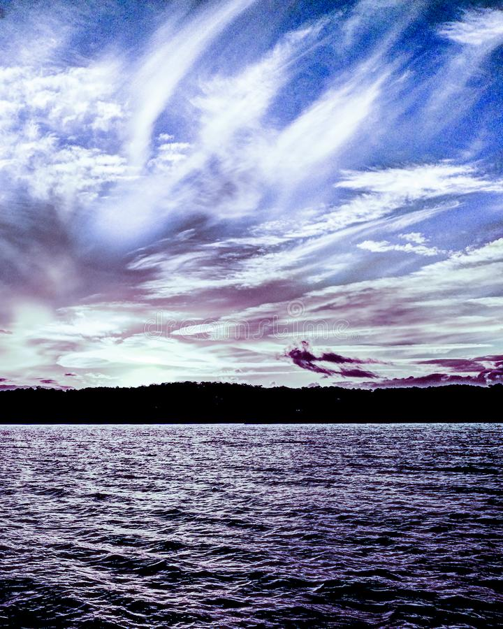Tranquil peaceful white and lilac cirrus cloud, coastal sunset s royalty free stock photo