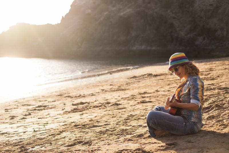 Beautiful and peaceful young woman sitting on the shore at the beach anjoying leisure activity on the sand playing an ukulele royalty free stock images