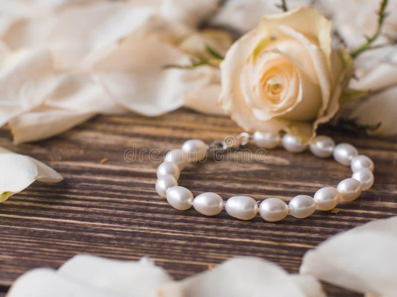 Beautiful pearl bracelet on elegant flower background, close up.  stock photography