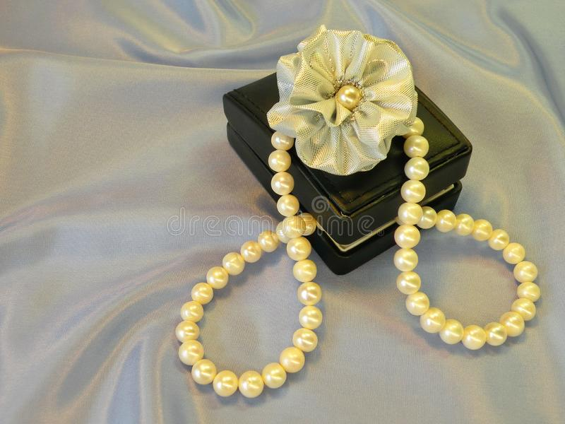 Pearls necklace, gift box and ribbon stock photos