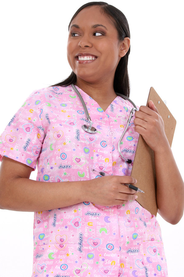 Beautiful Pediatric Nurse In Scrubs. Beautiful pediactric nurse in pink scrubs writing on clipboard. Look of concentration on face royalty free stock images