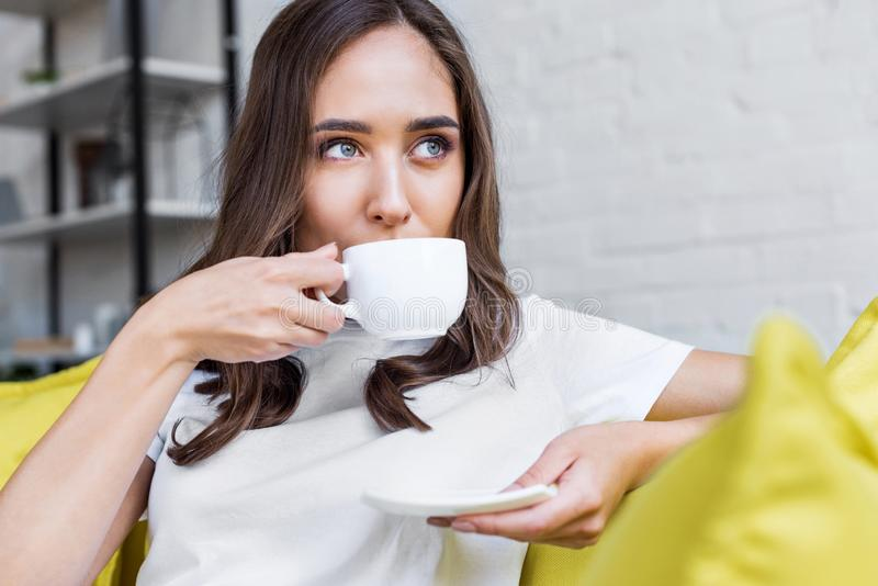 beautiful pensive brunette girl drinking coffee and looking away royalty free stock image