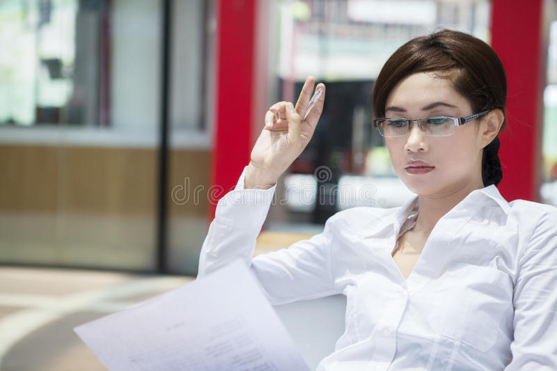 Beautiful pensive businesswoman at workplace stock image