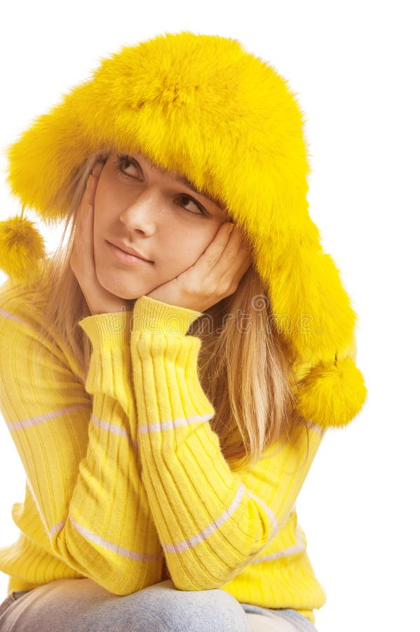 Beautiful pensive young woman in yellow fur hat stock photography