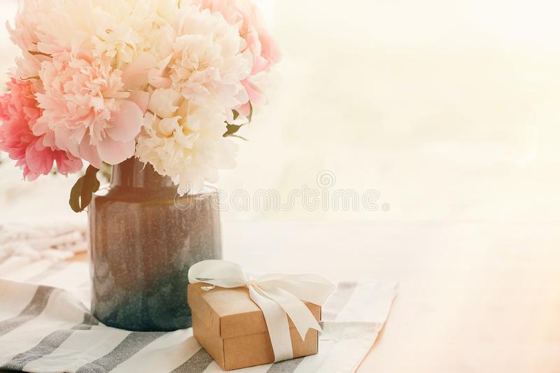Beautiful peonies in vase and gift box on rustic wooden table in sunny morning light with space for text. Happy mothers day stock photo