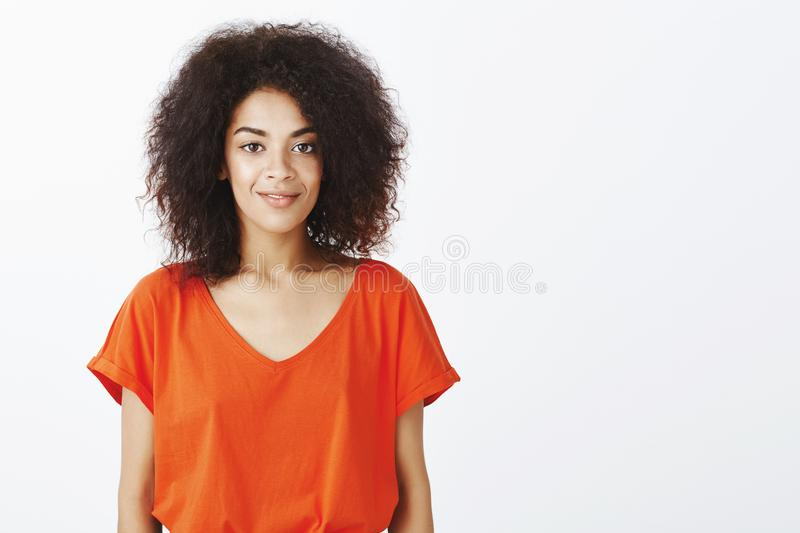 Beautiful people and positive emotions concept. Joyful good-looking dark-skinned model with afro hairstyle standing in stock photography