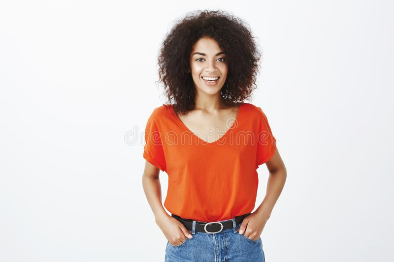 Beautiful people and positive emotions concept. Joyful good-looking dark-skinned model with afro hairstyle standing in. Stylish t-shirt and smiling happily at stock photos