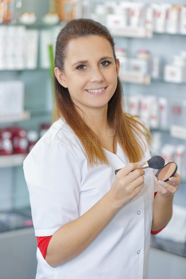 Beautiful pharmacist choosing product in drugstore stock photo