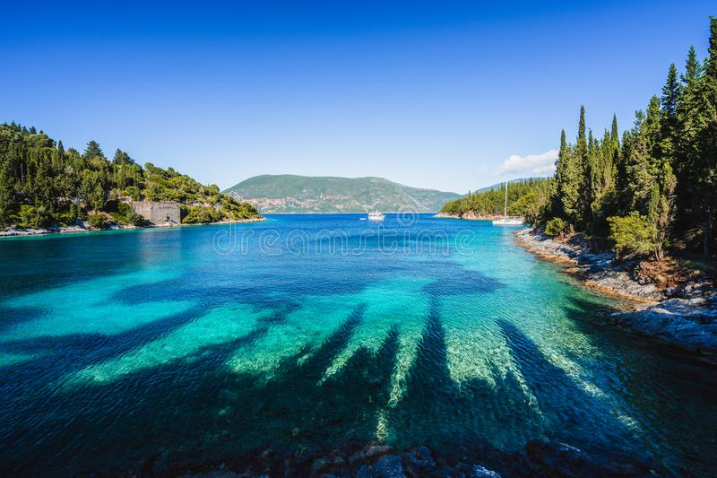 Beautiful Phoki Beach surrounded by cypress trees in the evening sunlight. Amazing seascape of Ionian Sea. Cypress royalty free stock photography