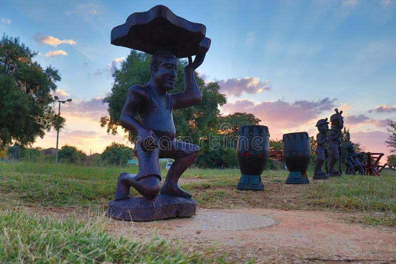 Statues in the Sunset. A beautiful photo of African Statues with the sun setting in the background. There`s also African drums and tables in the photograph royalty free stock photo