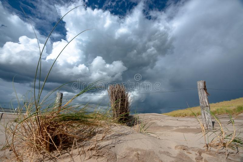 Impressive white and gray storm clouds over dune landscape along stock photo