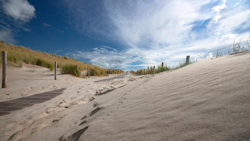 Impressive white and gray storm clouds over dune landscape along stock photos
