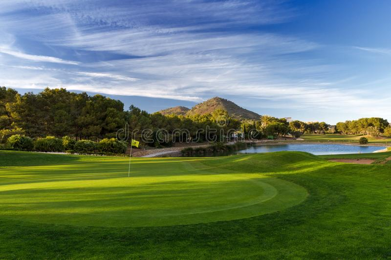 Golf course with trees, blue sky and mountains. A beautiful photo of a golf course with green grass and mountain. Blue sky and clouds. Photo taken in Spain in royalty free stock image