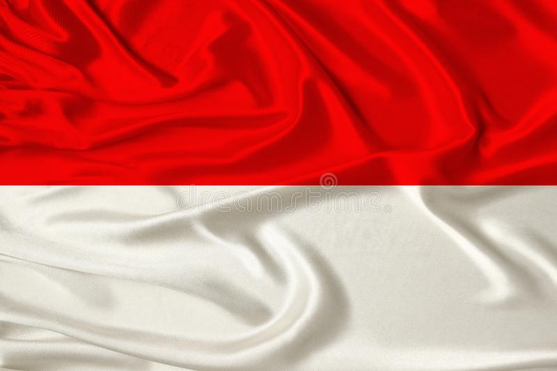 Beautiful photo of the national flag of Monaco and Indonesia on delicate shiny silk with soft draperies, the concept of state stock image