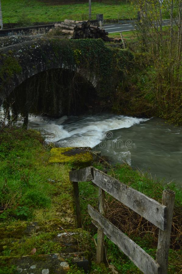Beautiful Photo Postcard With A Brave River, A Roman Bridge And A Mountain Of Freshly Cut Logs Wet By The Rain In Gorbeia Natural stock photography