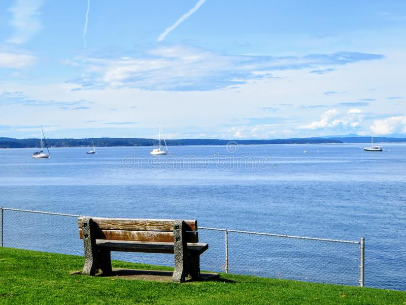 A beautiful photo of a wooden bench that looks outward to the ocean full of boats anchored on a calm sea royalty free stock photo