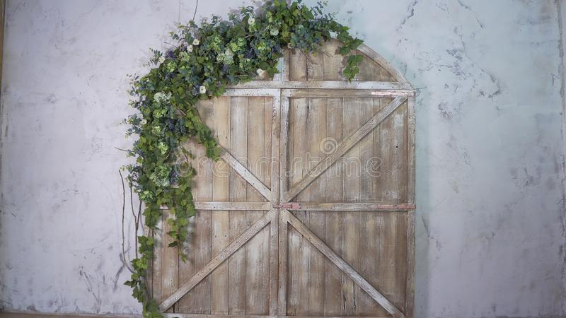 Beautiful photo zone: wooden gate and arch of flowers stock photography