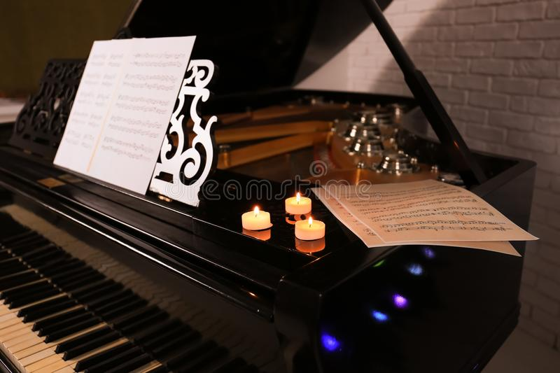 Beautiful piano with candles in room. Christmas concept stock image